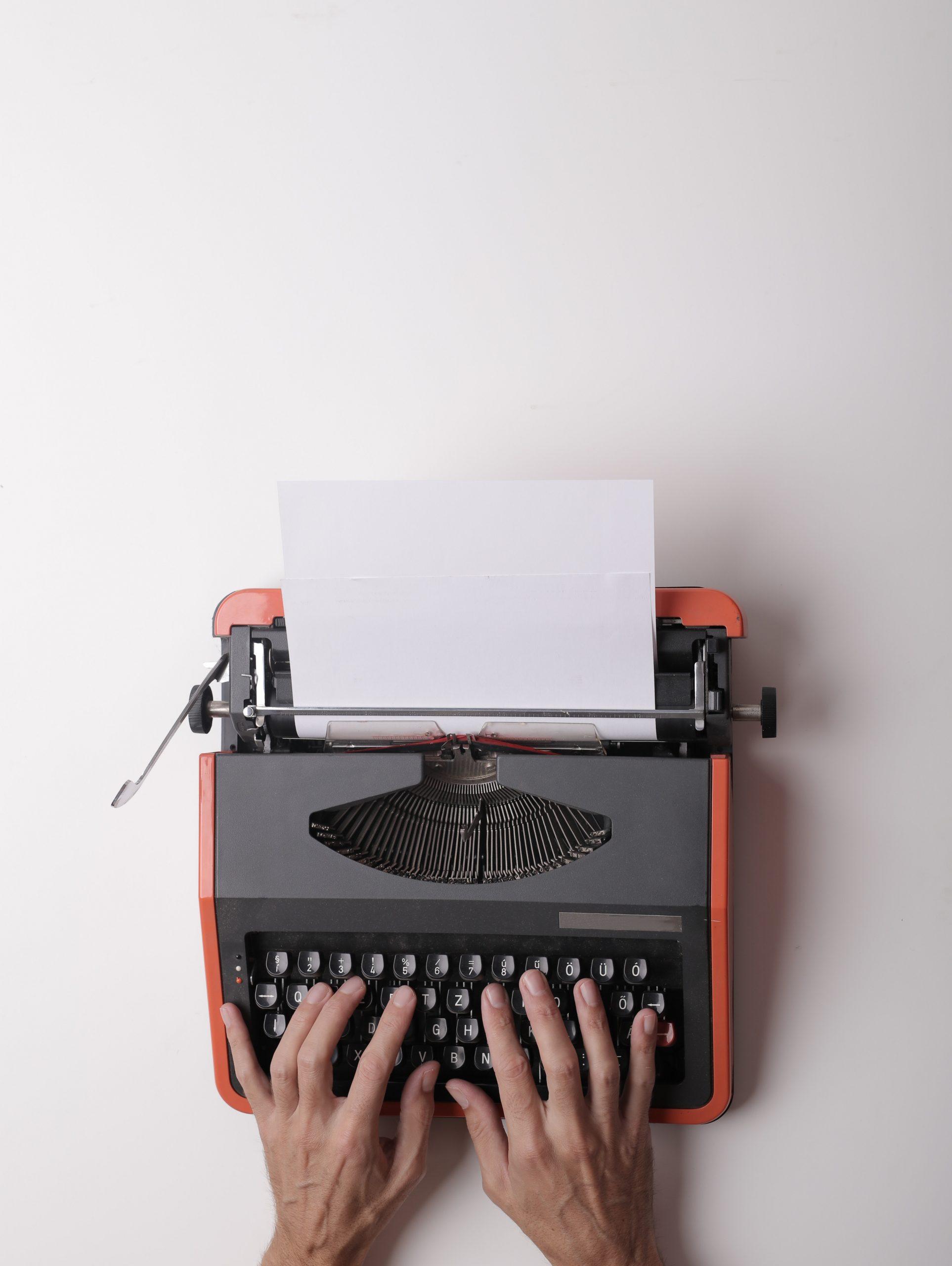 writer-working-on-typewriter-in-office-3808904
